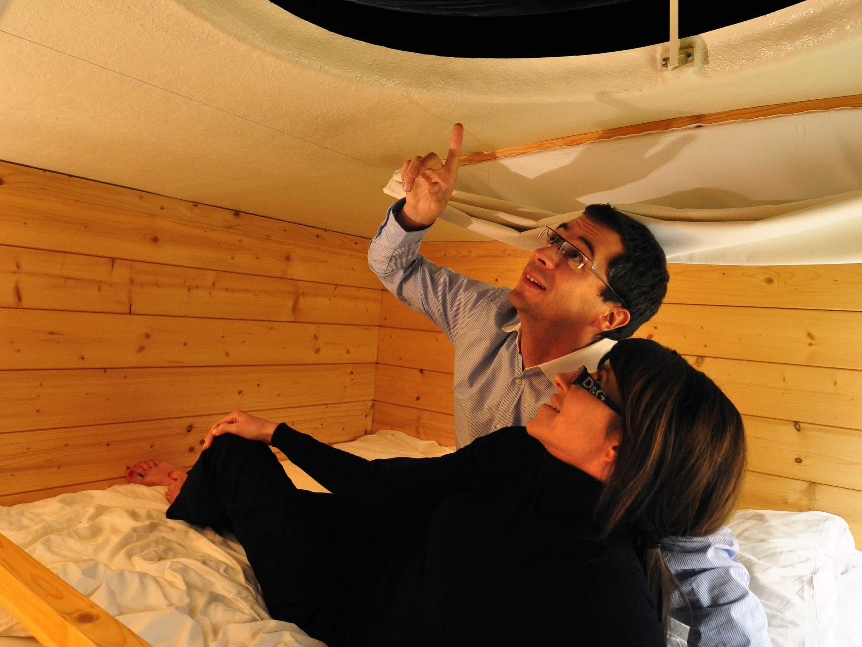 couple dans le lit en mezzanine avec vue sur les étoiles